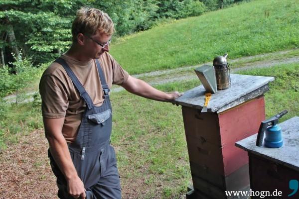 Imkermeister Achim Fuchs vor seinen Bienenstöcken. Obenauf der Smoker.