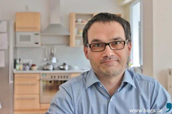 """Gottfried Stegbauer in seiner Wohnung über dem Geschäft. Im Hintergrund die Küche, wo der Chef selten anzutreffen ist: """"Ich bin ein schlechter Koch."""""""